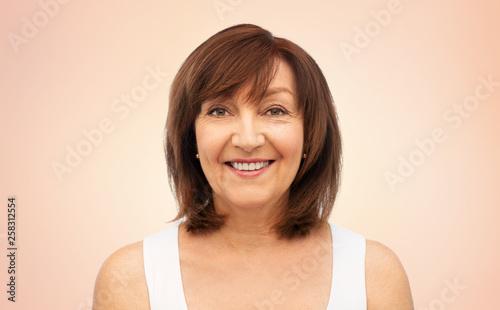 Leinwandbild Motiv beauty and old people concept - portrait of smiling senior woman over beige background