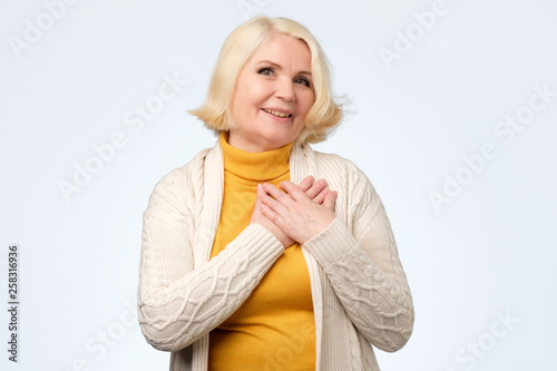 canvas print picture blonde woman with tender smile, keeps both palms on chest