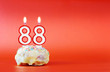 Eighty eight years birthday. Cupcake with white burning candle in the form of number 88. Vivid red background with copy space