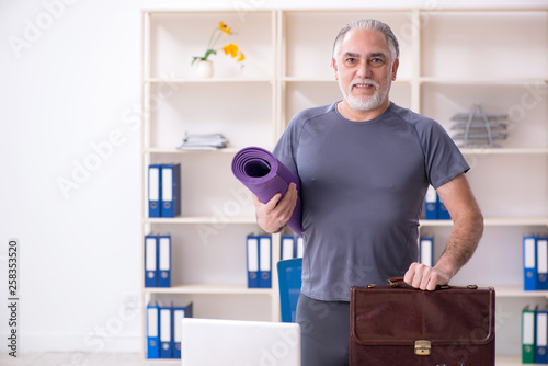 Leinwandbild Motiv White bearded old man employee doing exercises in the office