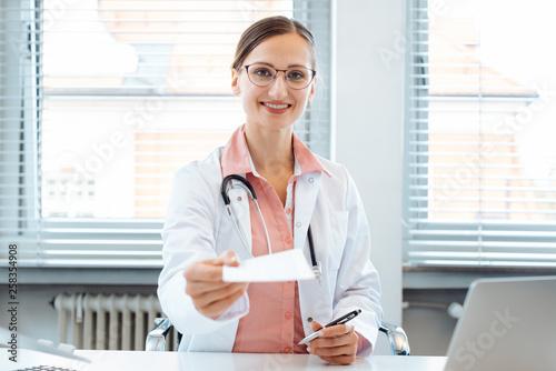 Leinwandbild Motiv Arzt halt ein Rezept für ein Medikament in die Kamera