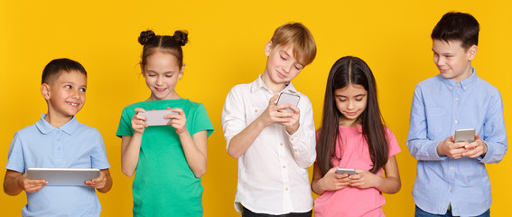 Gadget addiction. Children with modern gadgets, yellow background