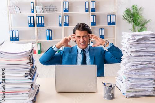 Leinwandbild Motiv Young handsome businessman unhappy with excessive work