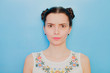 Funny cute girl on a blue studio background. Bright emotional female portrait. Angry soft face