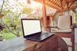 Leinwandbild Motiv Laptop on a home porch / patio with view to a garden.