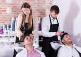 Men relaxing while hairdressers washing their hair