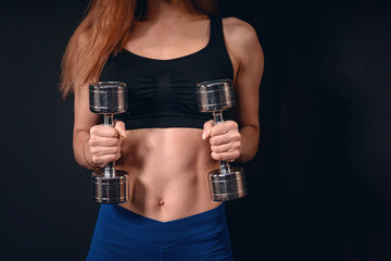 girl athletic lifts dumbbell. exercise for biceps with dumbbells. with free text space. © skif