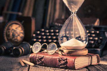 Hourglass and journal as memories of old journeys