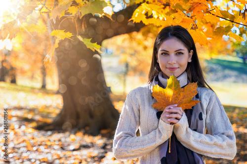 canvas print picture Jahreszeiten Konzept: Attraktive Frau im Park hält ein goldenes Herbstblatt in der Hand