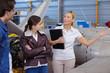 Leinwandbild Motiv mature woman giving tour of aircraft hangar
