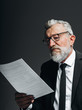 Leinwandbild Motiv Mature bearded businessman wearing spectacles in black suit reading holding document in his hand isolated on black