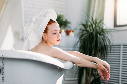 Leinwandbild Motiv Young redhead caucasian woman treats herself to a comforting warm bath, release tension, gets free her body of the everyday strains and stress.