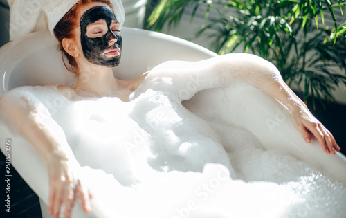 Leinwandbild Motiv Skin care - Young lady with facial black clay mask applyed on her face relaxing in foam bath, getting rejuvenation spa and beaty procedure at home