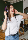 Brunette longhaired woman in headphones wearing white t-shirt enjoying her favorite music