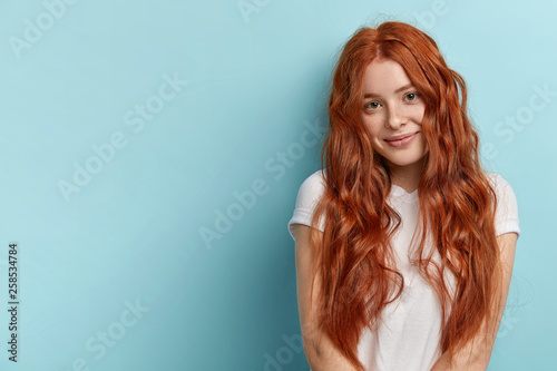 Leinwanddruck Bild Healthy hair and perfect freckled skin concept. Satisfied teenage girl with red wavy loose hair, gentle smile, wears white t shirt, isolated over blue wall, has natural beauty, poses for making photo