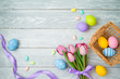 Easter holiday background with easter eggs in basket and tulip flowers on wooden table. - 258539333