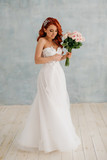 Happy red-haired bride stands with bouquet in her hands