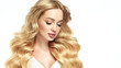 canvas print picture - Blonde girl with long  and   shiny wavy hair .  Beautiful  smiling woman model with curly hairstyle .