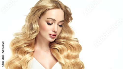 canvas print picture Blonde girl with long  and   shiny wavy hair .  Beautiful  smiling woman model with curly hairstyle .