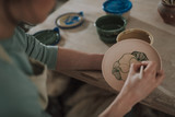 Young lady painting ceramic plate at workshop
