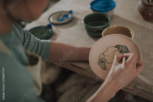 Young lady painting ceramic plate at workshop - 258607537
