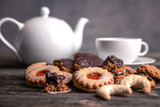 different homemade cookies with cup and pot of tea
