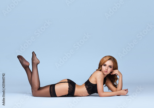 Young beautiful woman posing in sexy lingerie over colored background in studio. Girl in underwear. © Maksim Šmeljov