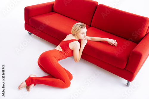 canvas print picture Beautiful magnetic woman sitting near the sofa