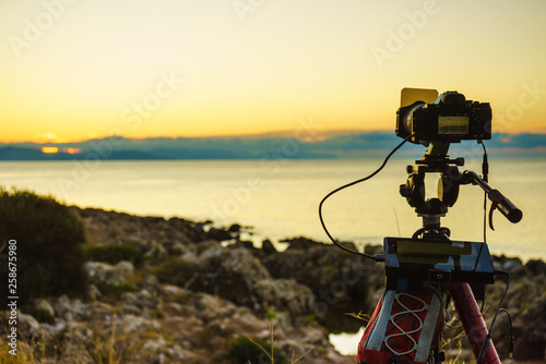 Camera taking picture film of sunrise over sea surface © anetlanda