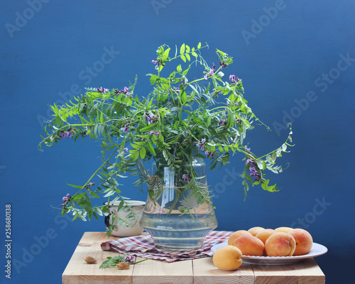 summer still life with flowers and fruit on a blue background. © MaskaRad