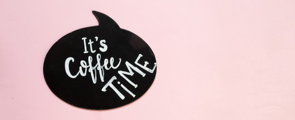 creative flat top view of a tablet holding an inscription pause coffee and a cup of coffee an alarm clock up on a pastel millennial pink paper background copy space. © shintartanya