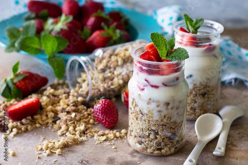 Homemade summer healthy breakfast. Greek yogurt with granola, pieces fresh strawberry on stone table.