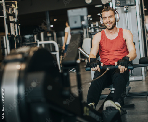Leinwandbild Motiv Young man doing workouts on a back with power exercise machine in a gym club