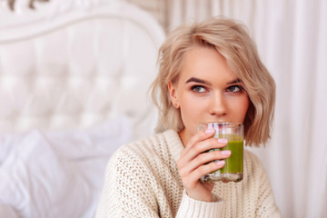 Blonde-haired woman drinking healthy green juice in bedroom © zinkevych