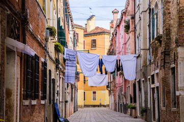 Narrow colourful street in Venice with clothes hanging drying