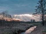 Fototapeta Fototapety na sufit - Promienie słońca przebijające się przez grubą warstwę ciemnych chmur. © boguslavus
