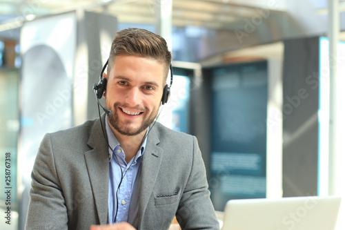 Smiling friendly handsome young male call centre operator. © ty