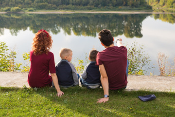 Childhood and nature concept - Family with little sons sitting on the green grass