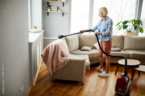 Serious attractive mature woman in homewear using vacuum cleaner while cleaning upholstery on sofa in living room © seventyfour