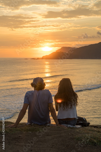 Leinwandbild Motiv Young romantic couple on vacation sitting and watching colorful sunset over the sea coast.