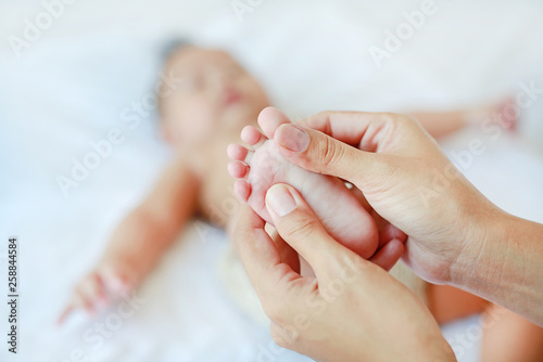 Leinwanddruck Bild Close-up baby foot massage on the bed.