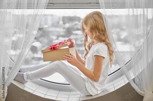Leinwandbild Motiv Little girl sitting on window and looking at present