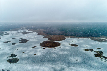 Frozen winter lake. On the lake there are many big and small islands.