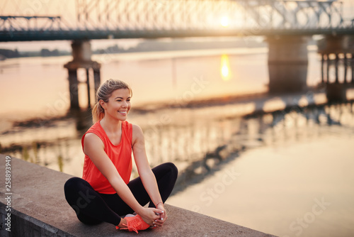 Leinwandbild Motiv Smiling Caucasian blonde woman in sportswear sitting on the wall on dock. In background bridge. Your health is an investment, not an expanse.