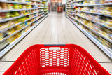 Red empty shopping cart in a supermarket aisle, motion blur