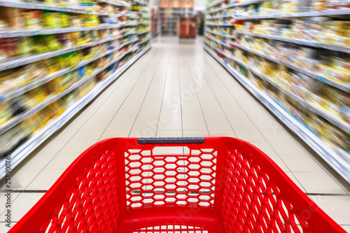 Red empty shopping cart in a supermarket aisle, motion blur © Delphotostock