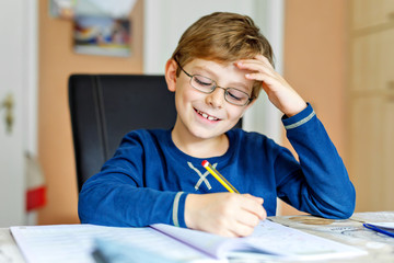 Portrait of cute school kid boy wearing glasses at home making homework. Little concentrated child writing with colorful pencils, indoors. Elementary school and education © Irina Schmidt