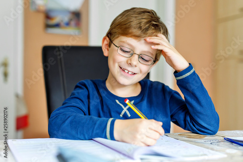 Zobacz obraz Portrait of cute school kid boy wearing glasses at home making homework. Little concentrated child writing with colorful pencils, indoors. Elementary school and education