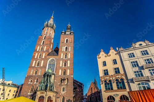 17/02/2019 Krakow, Poland, Catholic church Bazylika Mariacka on a sunny day with lots of tourists on the square near it