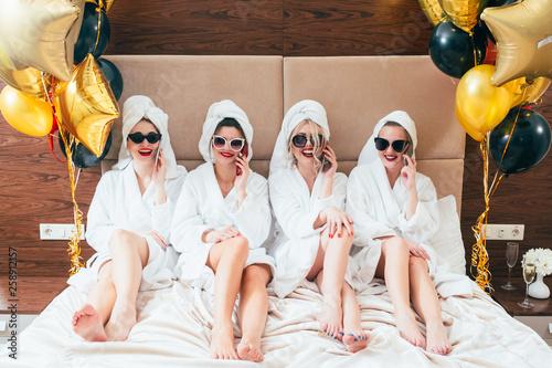 Leinwanddruck Bild Bathrobe party girls talking on smartphones. Urban females leisure lifestyle. Sunglasses and towel turbans on. Balloons.